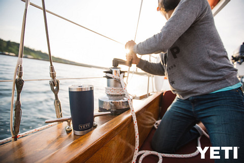 person operating sail boat with yeti tumbler